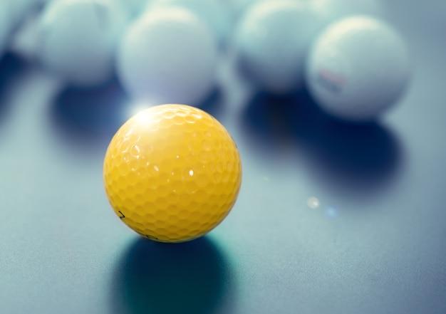 Białe i jedno żółte piłki golfowe na czarnej podłodze. koncepcja indywidualności i różnicy.