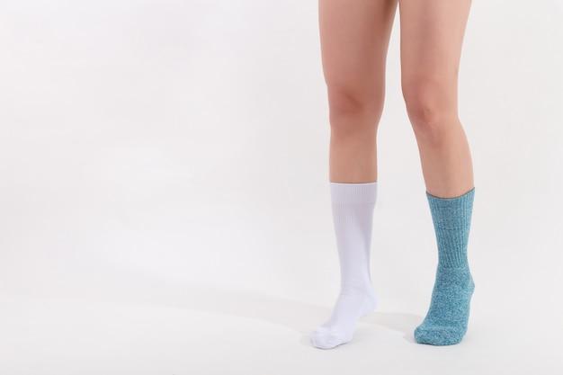 Białe i niebieskie bawełniane skarpetki na nogach pięknej kobiety.