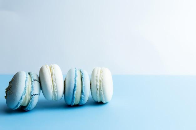 Białe i niebieskie makaroniki na stole, makaroniki na białym niebieskim tle.