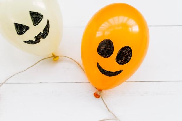 Białe i pomarańczowe balony powietrzne z przerażającymi, pomalowanymi twarzami