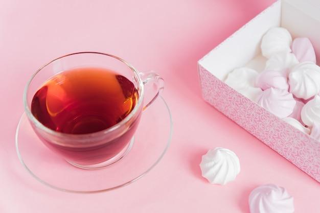Białe i różowe kręcone bezy i filiżankę herbaty na różowym tle