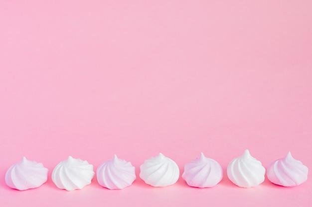 Białe i różowe kręcone bezy na różowym tle, kartka z pozdrowieniami, kopii przestrzeń