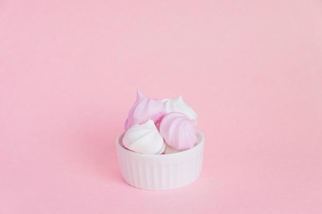 Białe i różowe kręcone bezy w porcelanowym pucharze na różowym tle, kartka z pozdrowieniami, kopii przestrzeń