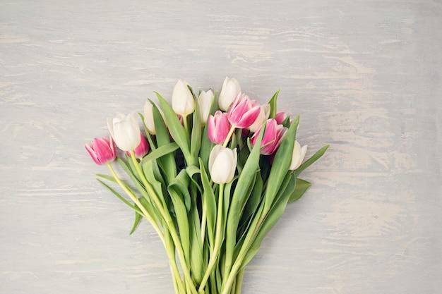 Białe i różowe kwiaty tulipanów na jasnej drewnianej ścianie. flat lay, top view minimalna świąteczna koncepcja wiosennych kwiatów