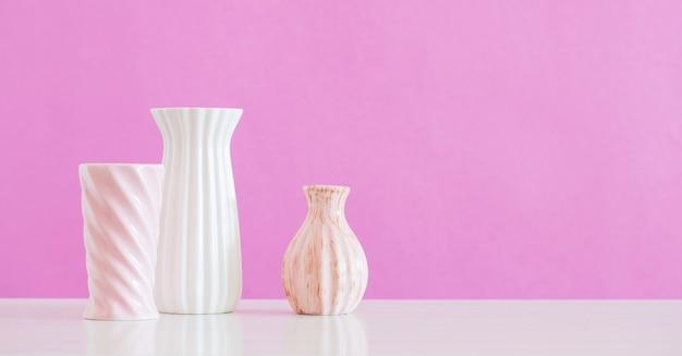 Białe i różowe wazony na różowym tle