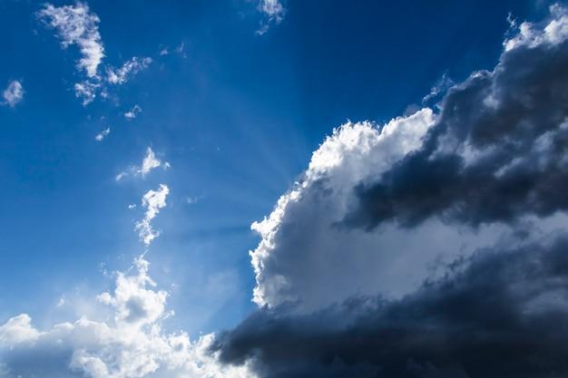 Białe i szare chmury, za którymi wznoszą się promienie słońca.
