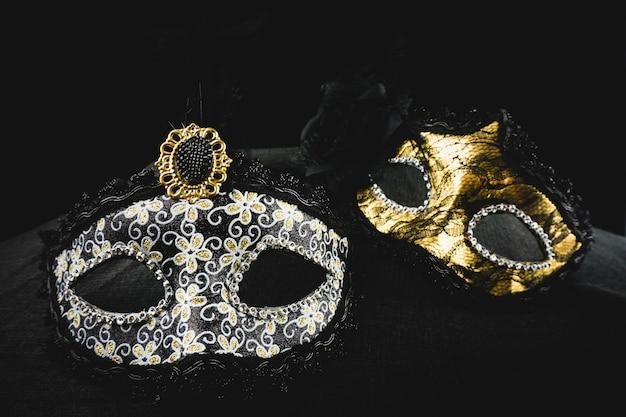 Białe i złote maski na ciemnym tle