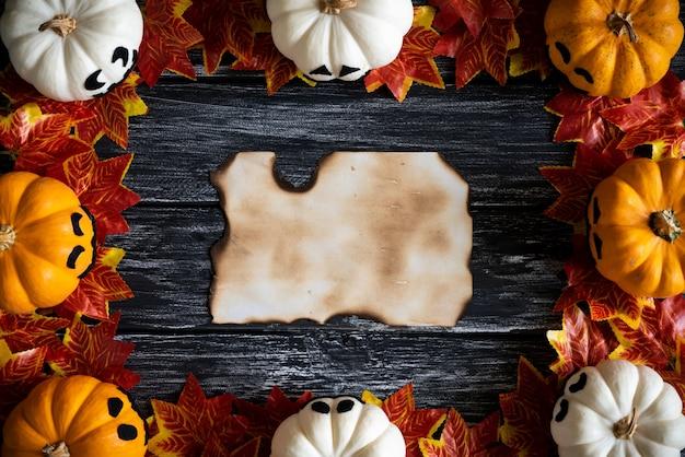 Białe i żółte duch dynie z liści jesienią i stary papier