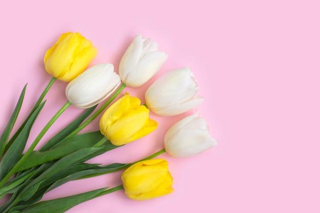 Białe i żółte tulipany na różowym tle.