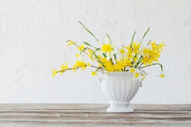 Białe i żółte wiosenne kwiaty w wazonie na powierzchni starej białej ściany