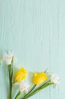 Białe irysy i żółte tulipany na zielonej drewnianej powierzchni