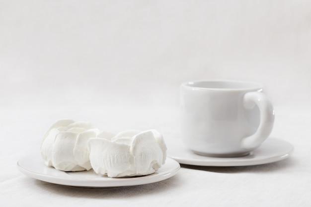 Białe jabłko zefir kwiaty na białym talerzu z filiżanką kawy
