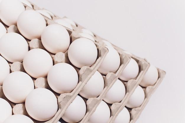 Białe jaja kury w nieszkodliwym, kartonowym opakowaniu