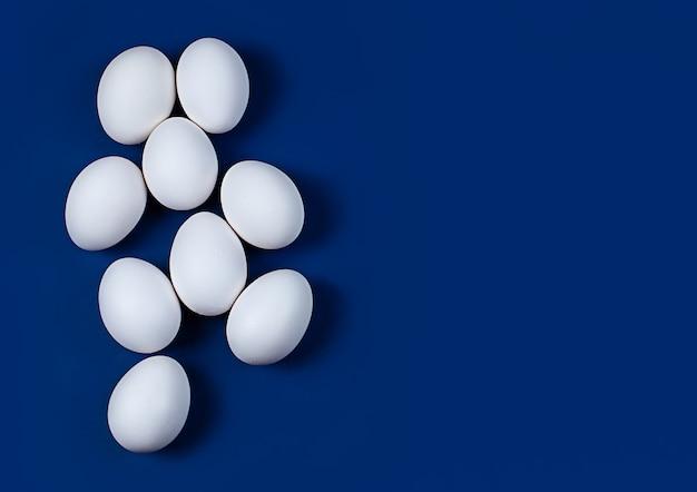 Białe jaja kurze dziewięć sztuk na niebieskim tle z miejscem na tekst