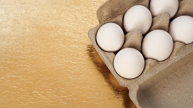 Białe jaja kurze w tekturowej tacy na złotym tle. tło z miejscem na tekst. zdrowa żywność i koncepcja wielkanocy. żywność białkowa