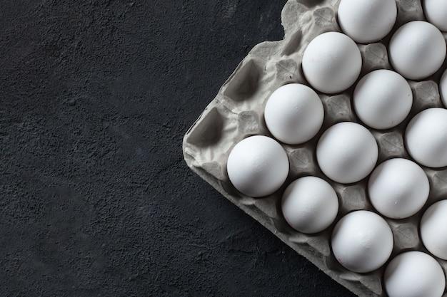 Białe jaja kurze w tekturowym pudełku na ciemnym tle betonu.