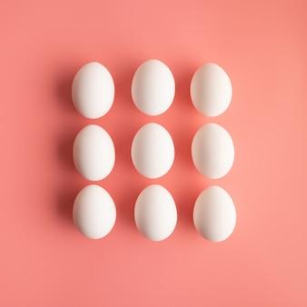 Białe jaja kurze w trzech rzędach kształtują prostokąt na minimalistycznym pastelowym różowym tle