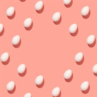 Białe jaja kurze wyrównane w rzędach oświetlone twardym światłem na pastelowym różowym tle
