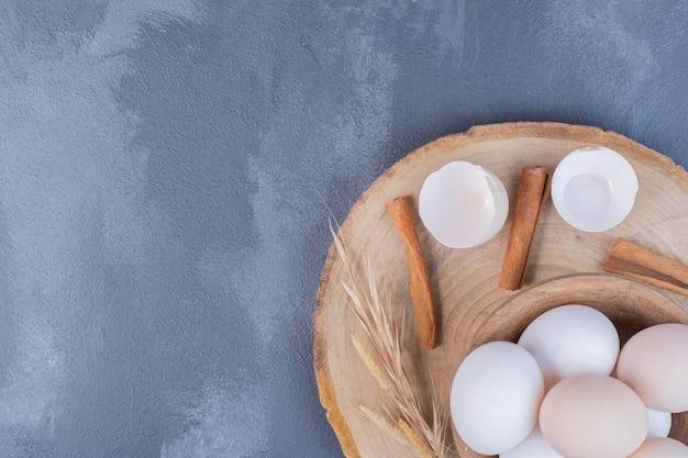 Białe jajka i skorupki na drewnianym półmisku.