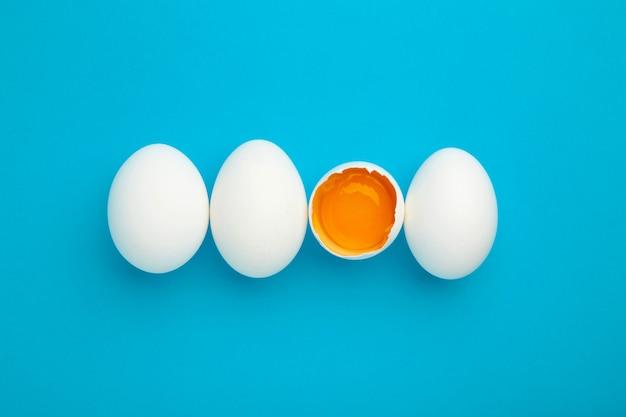 Białe jajka i żółtko na niebieskim tle.