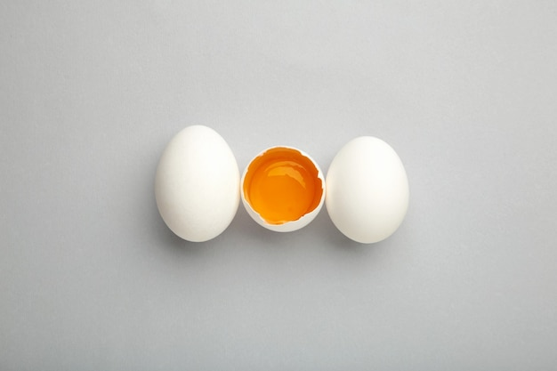 Białe jajka i żółtko na szarym tle.