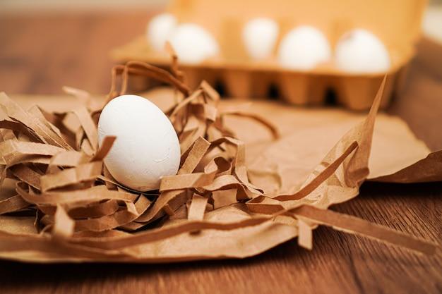 Białe jajka na brązowym papierze i na tacy na jajka na drewnianym stole