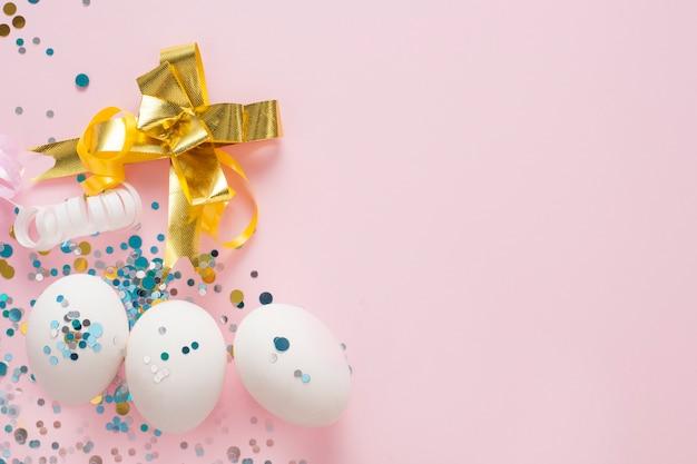 Białe jajka na różowym tle, ozdobione złotą kokardą, z miejsca kopiowania. wielkanocna koncepcja.