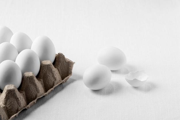 Białe jajka pod dużym kątem w kartonie