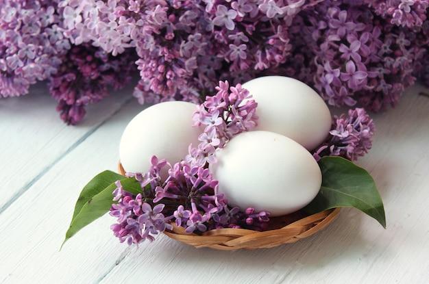 Białe jajka w liliowym koszu i wokół bukiet.