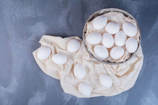 Białe jajka w metalowej filiżance i na ręczniku