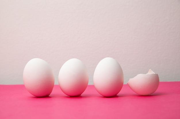 Białe jajka w pobliżu złamanej skorupy na różowym stole
