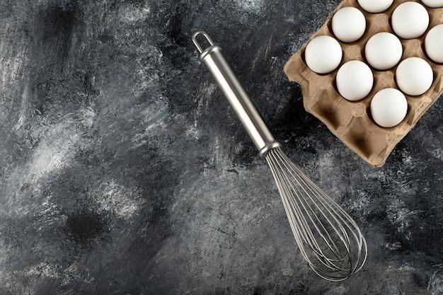 Białe jajka w tekturowym pojemniku i wąsy na marmurowej powierzchni.