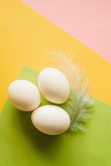 Białe jajka z szarymi piórami kurczaka na kolorowym żółtym, zielonym, różowym tle. leżał płasko, lato