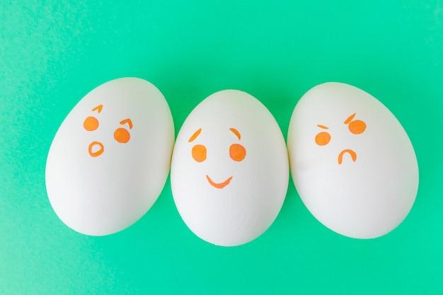 Białe jajka z uśmieszkami pomalowanymi markerami. emocje zaskoczenia, radości i gniewu.