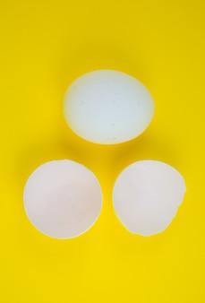 Białe jajko i skorupka na żółtym tle. skopiuj miejsce. minimalizm, oryginalne i kreatywne zdjęcie. piękna tapeta. święta wielkanocne.