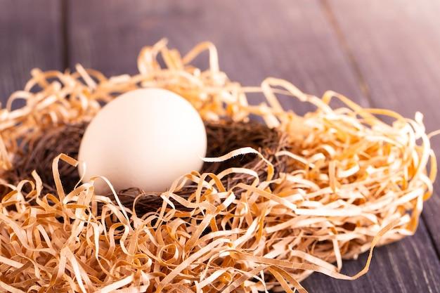 Białe jajko na gnieździe na starym drewnianym