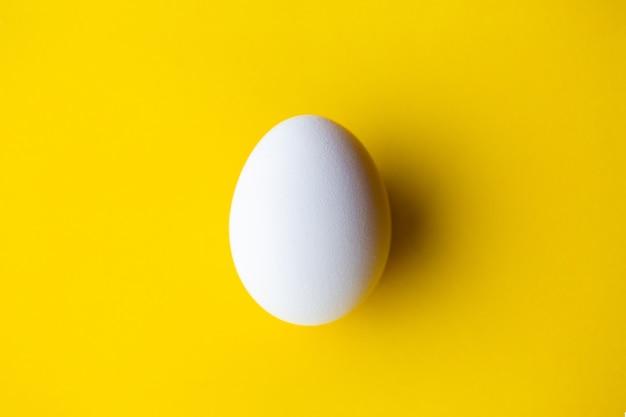 Białe jajko na żółtym tle.