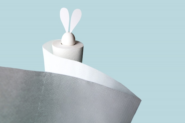 Białe jajko z uszami zająca w rolce papieru toaletowego. twardy cień na jasnym tle.