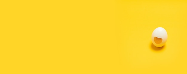 Białe jajko z wystrojem miłości serca na żółtym tle. karta składu wakacyjnego