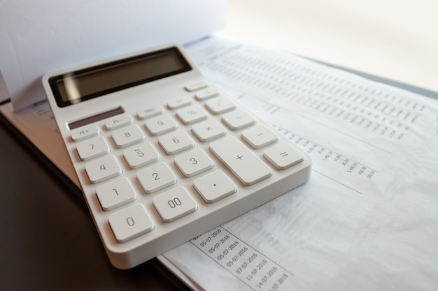 Białe kalkulatory i dokumenty finansowe na drewnianym biurku