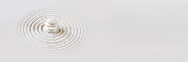 Białe kamienie piętrzą się w piasku. zen japoński ogród tło sceny. poziomy baner