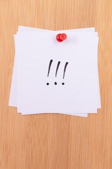 Białe karteczki samoprzylepne z trzema wykrzyknikami przypięte do drewnianej tablicy ogłoszeń
