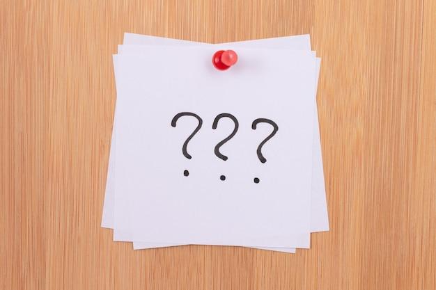 Białe karteczki samoprzylepne z trzema znakami zapytania przypięte do drewnianej tablicy dyskusyjnej