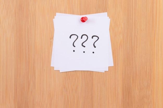 Białe karteczki samoprzylepne z trzema znakami zapytania przypiętymi do drewnianej tablicy dyskusyjnej. przypomnienie listy rzeczy do zrobienia w biurze. notatka w pracy