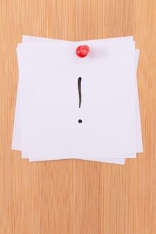 Białe karteczki samoprzylepne z wykrzyknikiem przypięte do drewnianej tablicy ogłoszeń