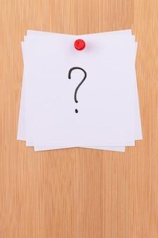 Białe karteczki samoprzylepne ze znakiem zapytania przypięte do drewnianej tablicy dyskusyjnej