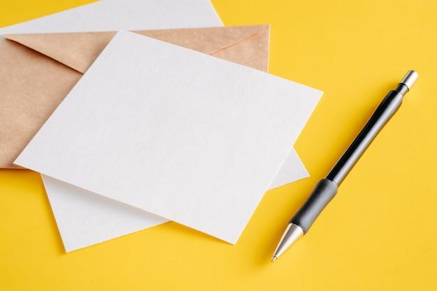Białe kartki papieru puste arkusze, koperta kraft i pióro na żółtym tle.