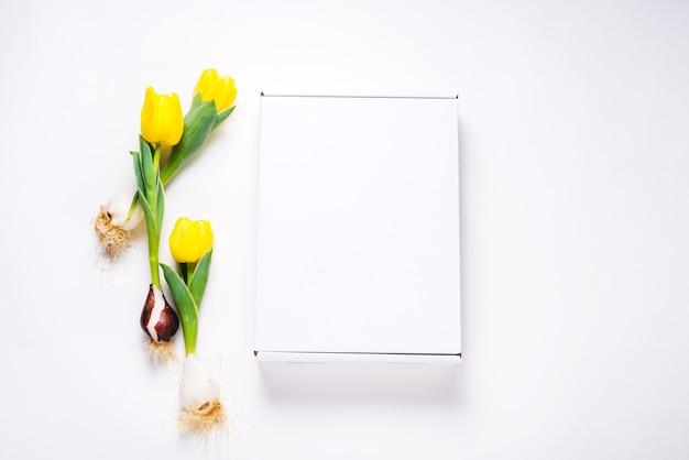 Białe kartonowe pudełko ozdobione świeżymi żółtymi tulipanami