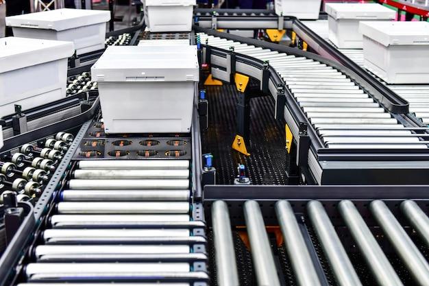 Białe kartony na przenośniku taśmowym. koncepcja koncepcji systemu transportu paczek