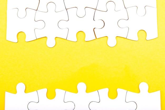 Białe kawałki układanki samodzielnie na żółtym tle